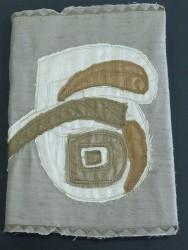 A shield made from carved and painted wood informed this machine embroidery