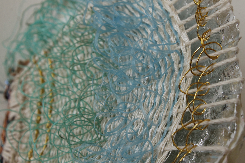 Mermaid weaving woven on a guilded scallop shell