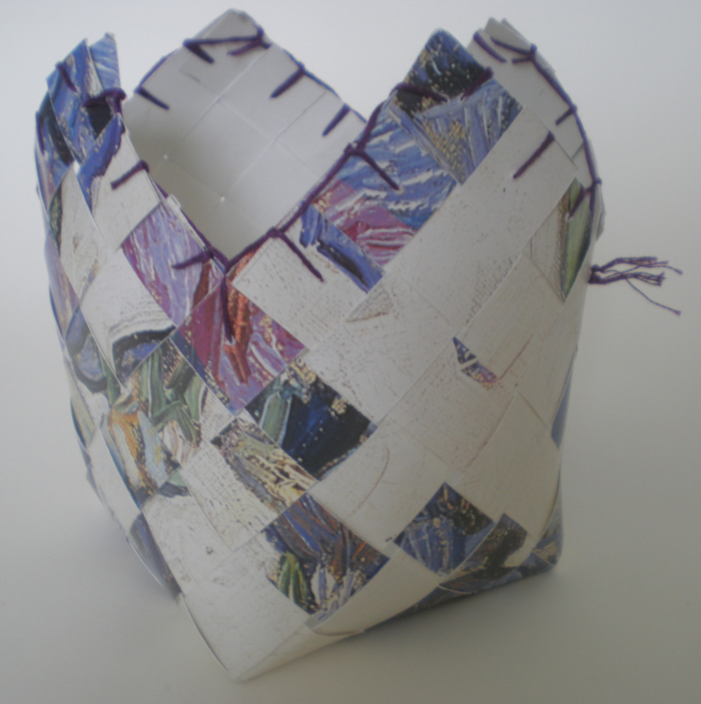 This basket was made with a badly printed Van Gogh poster of his Iris painting. The strips were cut, woven and stitched at the top to finish the basket.